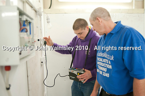 Student electrician tests his wiring with an instructor, Able Skills, Dartford, Kent.