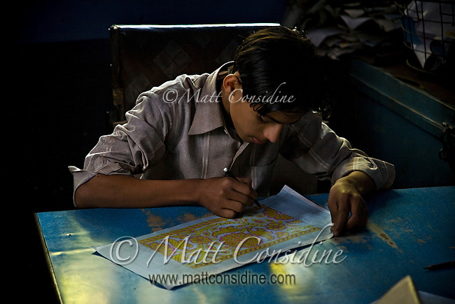Boy in workshop in the Muslim Quarter designing a pattern for weaving.<br /> (Photo by Matt Considine - Images of Asia Collection)