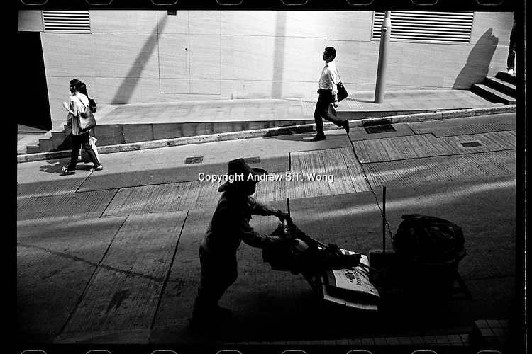 A cleaner pushes a trolley in Hong Kong's Central Financial District in September, 2011.