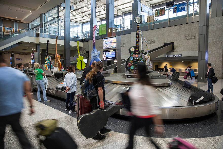 Travelers and passengers waiting for their luggage at the baggage carousel at Austin–Bergstrom International Airport. ABIA is a very cool airport to fly into with the 10- foot tall Gibson Guitars sitting on top of the number 3 Baggage Claim Carousel - Stock Image.