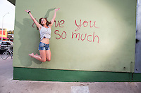 "Attractive Austin local woman jumps for joy at the ""i love you so much"" mural on South Congress Ave. (SoCo)."