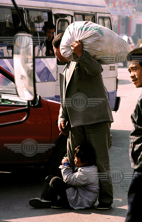 ©Mark Henley/Panos Pictures..China, Shanxi, Datong..Poverty. Persistent child beggar clinging on to man's legs as he tries to board bus.