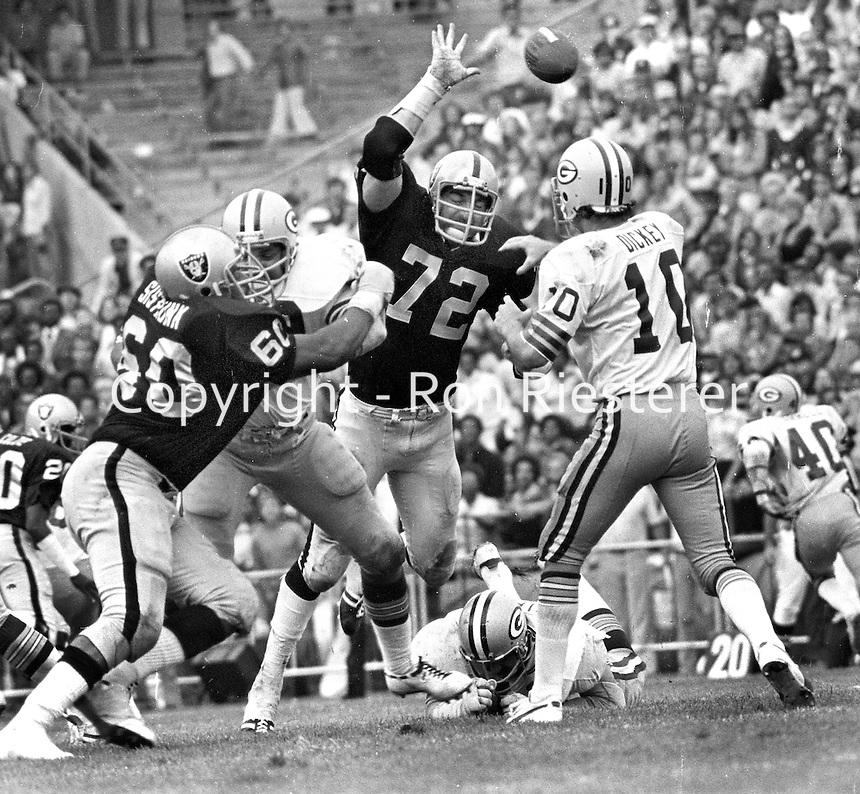 Raiders John Matuszak and Otis Sistrunk put rush on Green Bay Packers Lynn Dickey. (1976 photo by Ron Riesterer)