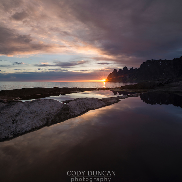 Midnight sun setting behind mountains at Tungeneset, Senja, Norway