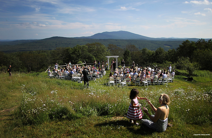 Laura Lippman of Baltimore with daughter Georgia Rae Simon, 3, picking daisies up on the hill looking over Novelist and writer Joyce Maynard and Jim Barringer's wedding ceremony in Harrisville, N.H., Saturday, July 6, 2013.  (Cheryl Senter for the New York Times)