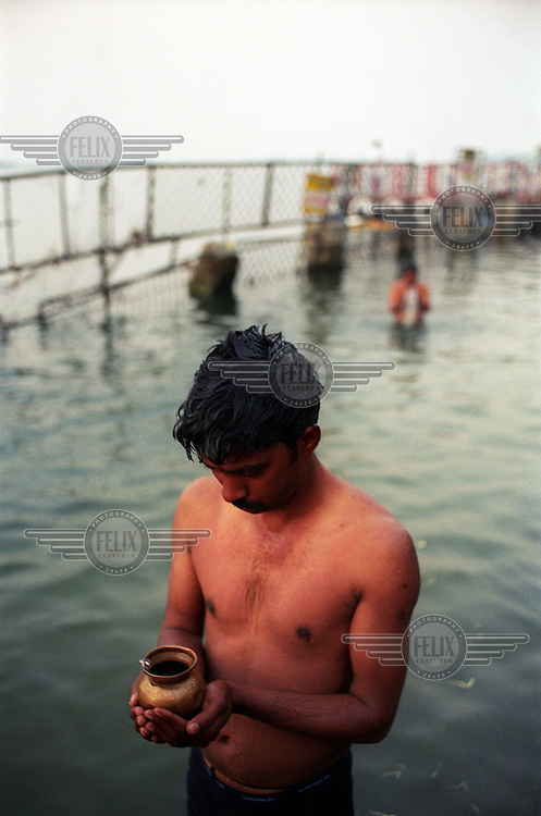 A man soon to become a father is cleansed before making his way up the hill to pray at one of the most important places of pilgrimage for Hindus, the Tirumala Venkateshwara Temple, the 'Holy Hill'.