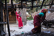 21 year old Asha Devi helps to clean up the house while her mother in law, Gita Devi takes care of her 11 month daughter, Sita Mandal in her house in Bhardaha in Saptari, Nepal.