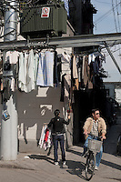 A Chinese woman hangs up her laundries at a traditional alleyway in Shanghai, China on November 06, 2009.