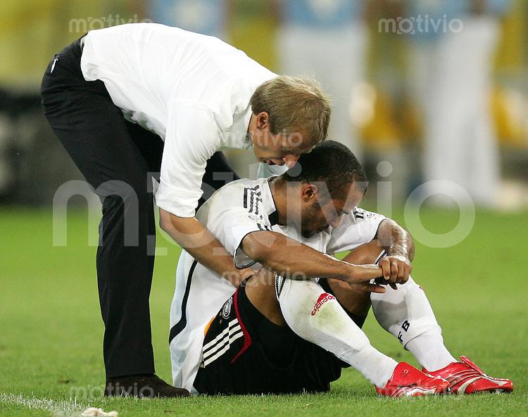 Fussball WM 2006 Halbfinale in Dortmund, Deutschland - Italien,  Bundestrainer Juergen Klinsmann troestet nach der 0:2. Niederlage David Odonkor.