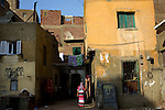 A woman walks to the entrance of her home, in Tora neighborhood in Cairo, Egypt, Aug. 5, 2009.