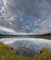 Early morning clouds form around the summit of Mt. Denali at the edge of Wonder Lake, Denali National Park, Alaska.