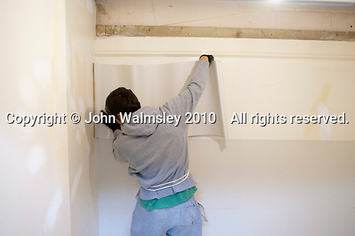 Painting & Decorating student hanging lining paper horizontally so the joins cannot line up with the joins of the wallpaper hung vertically on top, Able Skills, Dartford, Kent.