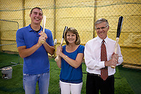 Brandon Nimmo, left, poses with his mother, Patti, and father, Ron, inside the family's 2688 sq. ft. barn on Tuesday, June 21, 2011, in Cheyenne, Wyo. The barn is home to a batting cage, pictured behind the Nimmos, where Nimmo perfected his left-handed swing growing up. (Photo by James Brosher)