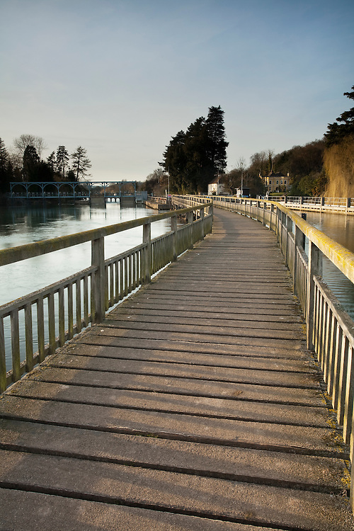 Looking along the wooden footbridge over the River Thames towards Marsh Lock near Henley on Thames in Oxfordshire, Uk