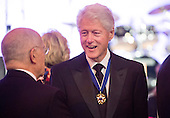 Former United States President Bill Clinton talks to guest during a dinner in honor of the Medal of Freedom awardees at the Smithsonian National Museum of American History on November 20, 2013 in Washington, D.C. <br /> Credit: Kevin Dietsch / Pool via CNP