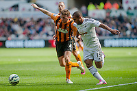 SWANSEA, WALES - APRIL 04: ( L-R )  Alex Bruce of Hull City  and Wayne Routledge of Swansea City  in action during the Premier League match between Swansea City and Hull City at Liberty Stadium on April 04, 2015 in Swansea, Wales.  (photo by Athena Pictures)