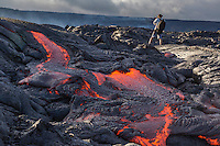 A hiker pauses to take some photographs of the lava flow, Hawai'i Volcanoes National Park, Hawai'i Island.