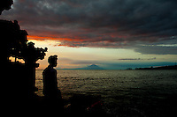 A Balinese man in traditional dress and headgear gazes toward Gunung Agung, Bali's sacred mountain.