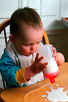 A toddler spills milk out of her sippy cup.