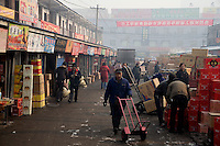Warehouse workers deliver boxes of goods to wholesalers in a market in Urumqi, Xinjiang, China.