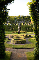 A view through to a knot garden enclosed by hedges and a leafy avenue, the tops of which make the hedges look like castellated walls