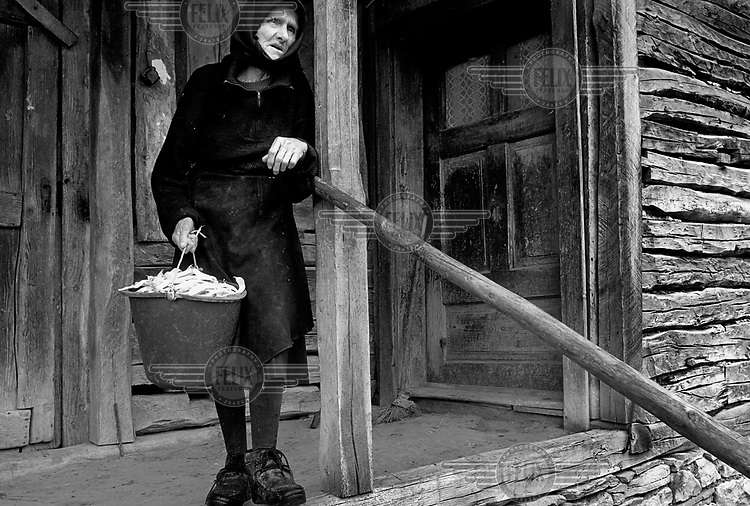 A elderly widow stands in front of her house in Bistrita.