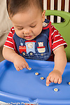 9 month old baby sitting in infant seat using pincer grasp to pick up Os cereal pieces