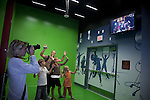 A family poses in front of a green screen while a woman takes a photo of their image on a monitor with a red carpet background at Madame Tussauds Hollywood, Los Angeles, CA