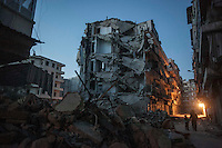 In this Sunday, Dec. 02, 2012 photo, night falls on the desolated streets of Bustan Al-Pasha neighborhood as Syrian residents walk among house buildings destroyed by heavy shelling and bombing during months of fighting in Aleppo, the Syrian's largest city. (AP Photo/Narciso Contreras)