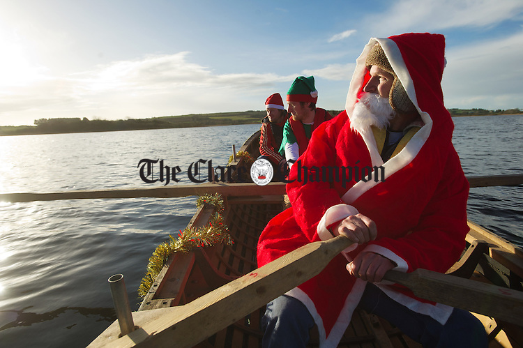 Kildysart's Pa Mc Mahon,(Santa) with colleagues, Peter Ranalow and Mark Ranalow of Kildysart Currach Club encouraging participants during the annual Christmas Day Swim In Gortglas lake. Photograph by John Kelly.