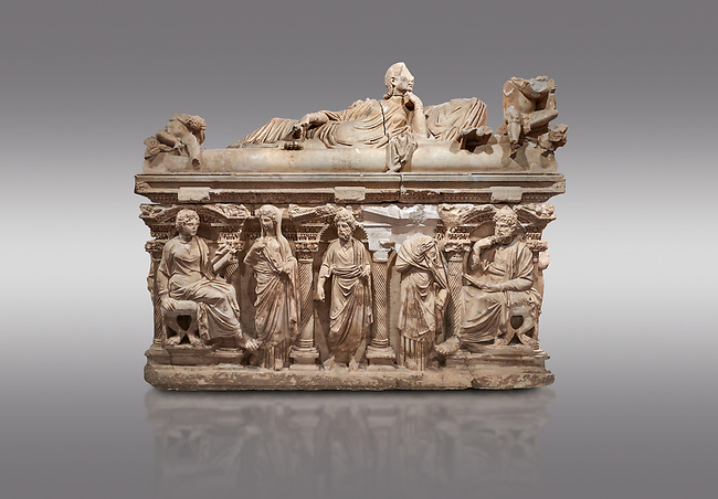"""Roman relief sculpted sarcophagus of Domitias Julianus and Domita Philiska depicted reclining on the lid, 2nd century AD, Perge. Antalya Archaeology Museum, Turkey.. Against a grey background.<br /> <br /> it is from the group of tombs classified as. """"Columned Sarcophagi of Asia Minor"""". <br /> The lid of the sarcophagus is sculpted into the form of a """"Kline"""" style Roman couch on which lie Julianus &  Philiska. This type of Sarcophagus is also known as a Sydemara Type of Tomb."""