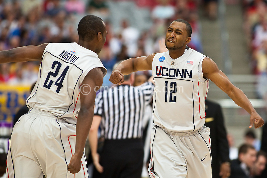 Mar 28, 2009; Glendale, AZ, USA; Connecticut Huskies guard A.J. Price (12) reacts to guard Craig Austrie's (24) made three-pointer in the first half of a game against the Missouri Tigers in the finals of the west region of the 2009 NCAA basketball tournament at University of Phoenix Stadium.  The Huskies defeated the Tigers 82-75 to advance to the Final Four in Detroit.