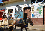 Two Nicaraguan men are pulled by a horse past revolutionary murals in Leon, Nicaragua