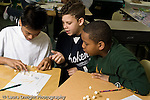 Education Elementary school Grade 5 class with science specialist making models from toothpicks and mini marshmallows three male students working together horizontal