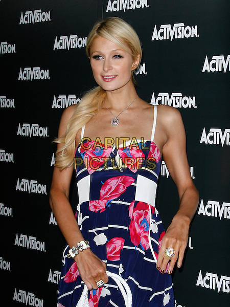 PARIS HILTON.Activision E3 2010 Preview Event held at the Staples Center, Los Angeles, California, USA. .June 14th, 2010 .half length dress white blue black floral print white striped stripes.CAP/ROT/MC.©Max Cash/Roth Stock/Capital Pictures