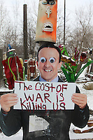 "manichino con cartello ""il costo della guerra ci sta uccidendo"" the cost of war is killing us"