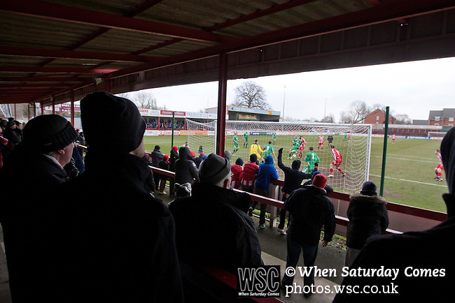 Altrincham 2 Worcester City 0, 23/03/2013. Moss Lane, Blue Square Bet North. Home team supporters watching on from the covered terracing behind the goal as their team try to score the opening goal during the second-half of the the Blue Square Bet North fixture between Altrincham (in red) and Worcester City at Moss Lane, Altrincham. The home team won the match 2-0 watched by 777 spectators on a day when most non-League football in England was cancelled due to adverse weather. Altrincham were historically one of the major English non-League teams but have never been promoted to the Football League. Photo by Colin McPherson.