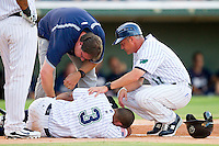 Charlotte Knights trainer Joe Geck and manager Joe McEwing #11 check on the status of Eduardo Escobar after he fouled a ball off his leg during the game against the Durham Bulls at Knights Stadium on August 2, 2011 in Fort Mill, South Carolina.  The Bulls defeated the Knights 18-3.   (Brian Westerholt / Four Seam Images)