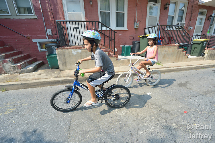 Enmanuel Curino and his sister Elianys ride their bikes on the street near their home in Lancaster, Pennsylvania. Refugees from Cuba, they and their family were resettled in Lancaster by Church World Service. <br /> <br /> Photo by Paul Jeffrey for Church World Service.