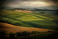 Farmland comprised of large rolling fields in the Tuscan countryside of Italy