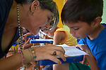 Marta Barral, a Xavierian lay missionary from Spain, helps a boy read during an educational program sponsored by the Catholic Church in Atalaia do Norte in Brazil's Amazon region. The afterschool tutoring program helps kids keep up with their school work.