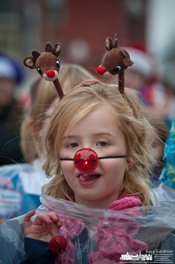 Young girl with reindeer antlers and a flashing red nose as part of a Girl Scouts Pack in the Westerville Christmas Parade