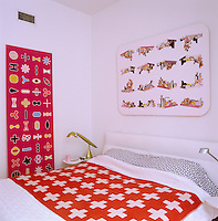 The computer generated artwork which surrounds the bed adds humour and colour to an otherwise white bedroom