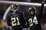 Essang Bassey (21) and Ja'Sir Taylor (24) of the Wake Forest Demon Deacons celebrate after Bassey intercepted a pass late in the fourth quarter to secure the win over the North Carolina State Wolfpack at BB&T Field on November 18, 2017 in Winston-Salem, North Carolina.  The Demon Deacons defeated the Wolfpack 30-24.  (Brian Westerholt/Sports On Film)