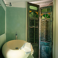 A rustic style green bathroom with painted doors. A deep round washbasin stands on a shelf in one corner.