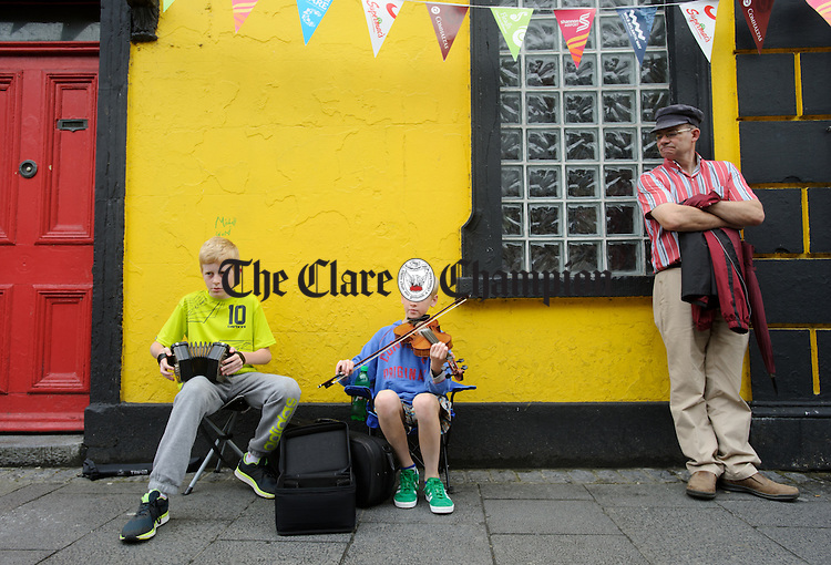 Cormac Egan and Fionnan O Sullivan of Quin perform watched by Tim Donovan O Clonakilty, o O Connell street, Ennis during Fleadh Cheoil na hEireann. Photograph by John Kelly.