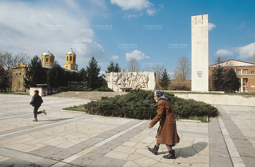 Bulgaria. Province Oblast Lovech. Lukowit. Town centre. An old woman with a blue headscarf walks on the main square near various monuments, which are all old communist symbols. A young boy runs ahead. An orthodox church. © 1997 Didier Ruef