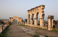The Triumphal Arch of Caracalla, built 217 AD by the city's governor Marcus Aurelius Sebastenus in honour of Emperor Caracalla, 188-217 AD, and his mother Julia Domna, and the main street or Decumanus Maximus with a section of its Portico leading to the shops, Volubilis, Northern Morocco. Volubilis was founded in the 3rd century BC by the Phoenicians and was a Roman settlement from the 1st century AD. Volubilis was a thriving Roman olive growing town until 280 AD and was settled until the 11th century. The buildings were largely destroyed by an earthquake in the 18th century and have since been excavated and partly restored. Volubilis was listed as a UNESCO World Heritage Site in 1997. Picture by Manuel Cohen