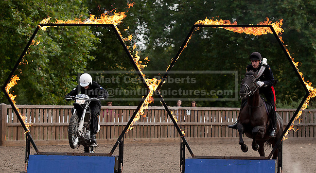 12/09/2012. LONDON, UK. Household Cavalry Lance Corporal of Horse Josh Tate, on his horse Evolution, and Royal Signals Corporal Daniel Hale jump through flaming rings in Hyde Park London today (12/09/12) during a taster of some of the acts taking part in the 2012 British Military Tournament. The theme of this year's tournament, involving all arms of the British military, is the life and times of Her Majesty the Queen and takes place at Earls Court in London on the 8th and 9th of December. Photo credit: Matt Cetti-Roberts