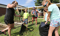 NWA Democrat-Gazette/DAVID GOTTSCHALK Sarah Boyd (from left), garden volunteer coordinator, works Wednesday, July 10, 2019, with Felix Suel, 8, Meranda (cq) Bowlin, Ella Bowlin, 8, and Pippi Suel, 11, as they clear the last weeds and grass from the Tyson Edible Garden at John Tyson Elementary School in Springdale. Neighbors and families are encouraged to harvest the ripe vegetables from the garden that was established in 2015.